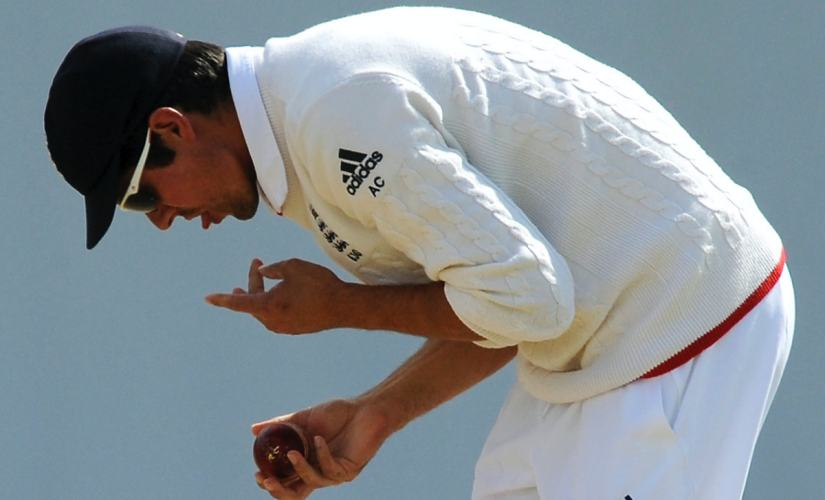 In this July 30, 2015, file photo England captain Alastair Cook polishes the ball during their Ashes Test cricket match against Australia in Birmingham, England. A move to ban the use of saliva to shine a cricket ball because of the danger of transmitting Covid-19 may force bowlers to relearn or reinvent one of the sportÅfs most prized but troublesome skills. (AP Photo/Rui Vieira, FILE)