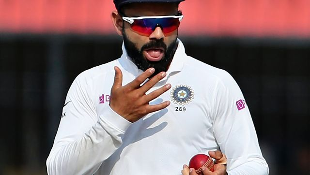 In this Nov. 16, 2019, file photo India's captain Virat Kohli shines the ball during their cricket test match against Bangladesh in Indore, India. A move to ban the use of saliva to shine a cricket ball because of the danger of transmitting Covid-19 may force bowlers to relearn or reinvent one of the sportÅfs most prized but troublesome skills. (AP Photo/Aijaz Rahi, FILE)