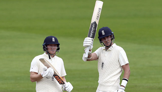 England's Stuart Broad, right, raises his bat to celebrate scoring fifty runs during the second day of the third cricket Test match between England and West Indies at Old Trafford in Manchester, England, Saturday, July 25, 2020. (Michael Steele/Pool via AP)