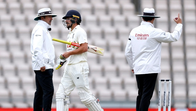The umpire raises his finger as England's Rory Burns, center, leaves the field after being dismissed by West Indies' Shannon Gabriel during the second day of the first cricket Test match between England and West Indies, at the Ageas Bowl in Southampton, England, Thursday, July 9, 2020. (Adrian Dennis/Pool via AP)