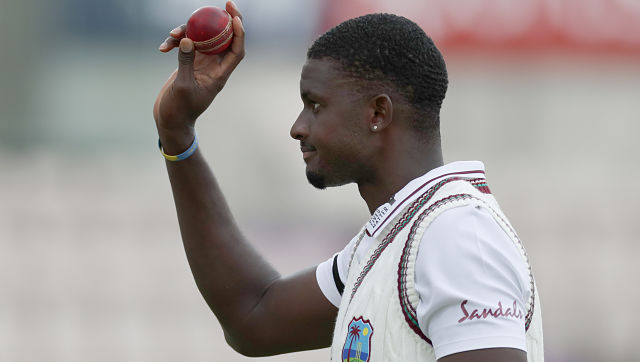 West Indies' captain Jason Holder holds up the ball as he leaves the field after taking six wickets during the second day of the first Test against England. AP Photo