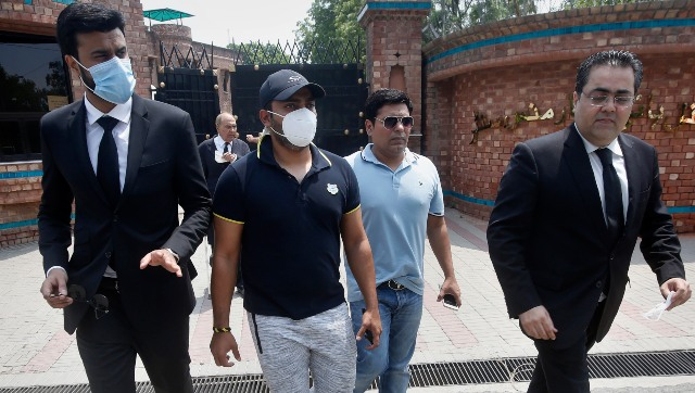 Pakistani cricketer Umar Akmal, center, arrives with his lawyers at the Pakistan Cricket Board office in Lahore, Pakistan, Wednesday, July 29, 2020. An independent adjudicator has halved batsman Akmal's ban to 18 months for failing to report corrupt approaches before this year's Pakistan Super League. (AP Photo/K.M. Chaudhry)