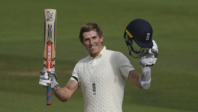 England's Zak Crawley raises his bat and helmet to celebrate scoring a century during the first day of the third cricket Test match between England and Pakistan, at the Ageas Bowl in Southampton, England, Friday, Aug. 21, 2020. (Mike Hewitt/Pool via AP)