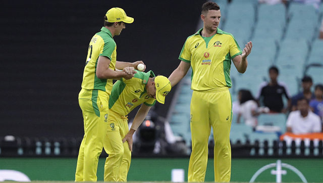 Australia's David Warner is assisted by teammates after injuring himself during second ODI against India. AP
