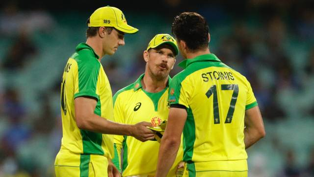Australian captain Aaron Finch, centre, talks to bowlers Pat Cummins, left, and Marcus Stoinis during the one day international cricket match between India and Australia at the Sydney Cricket Ground in Sydney, Australia, Friday, Nov. 27, 2020. (AP Photo/Rick Rycroft)