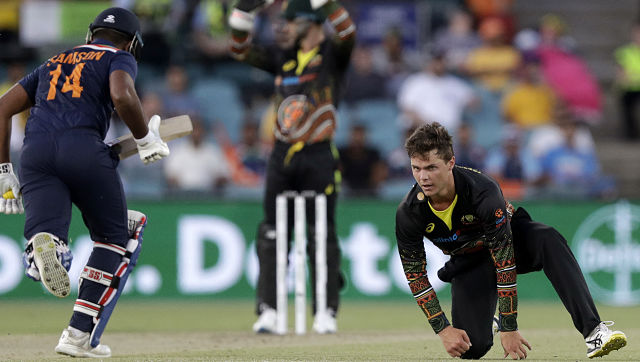 Australia's Mitchell Swepson, right, watches the ball run after an attempt to field against India's during their T20 international cricket match at Manuka Oval, in Canberra, Australia, Friday, Dec 4, 2020. (AP Photo/Mark Baker)