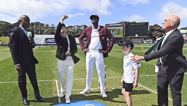 New Zealand's captain Tom Latham, second left, and West Indies' captain Jason Holder, center, toss the coin before play on the first day of their second cricket test in Wellington, New Zealand, Friday, Dec. 11, 2020. (Andrew Cornaga/Photosport via AP)