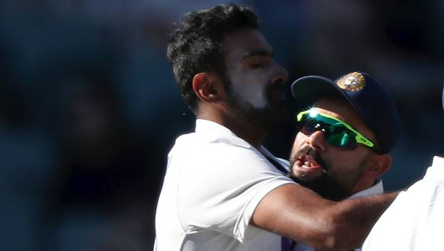 India's Ravichandran Ashwin, left, is hugged by his captain Virat Kohli after taking the wicket of Australia's Steve Smith for 1 run on the second day of their cricket test match at the Adelaide Oval in Adelaide, Australia, Friday, Dec. 18, 2020. (AP Photo/James Elsby)