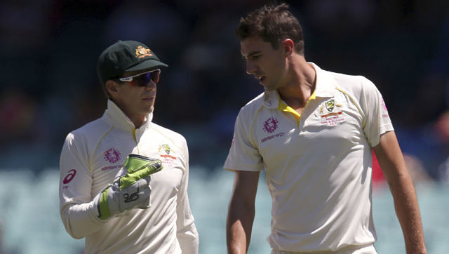 Australia's captain Tim Paine, left, gives instructions to his bowler Pat Cummins on day 2 during their cricket test match against India in Sydney, Friday, Jan. 4, 2019. (AP Photo/Rick Rycroft)