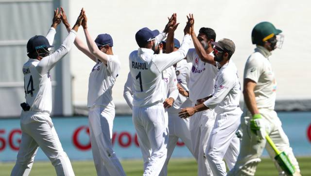 Indian players celebrate the dismissal of Australia's Tim Paine, right, during play on day one of the Boxing Day cricket test between India and Australia at the Melbourne Cricket Ground, Melbourne, Australia, Saturday, Dec. 26, 2020. (AP Photo/Asanka Brendon Ratnayake)