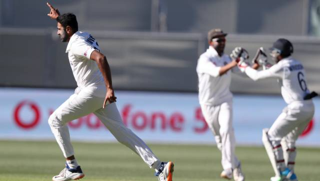 India's Ravichandran Ashwin, left, celebrates taking the wicket of Australia's Steve Smith for 1 run on the second day of their cricket test match at the Adelaide Oval in Adelaide, Australia, Friday, Dec. 18, 2020. (AP Photo/James Elsby)