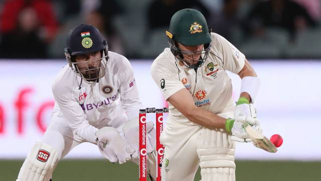 Australia's Tim Paine, right, plays a shot in front of India's Wriddhiman Saha on the second day of their cricket test match at the Adelaide Oval in Adelaide, Australia, Friday, Dec. 18, 2020. (AP Photo/James Elsby)