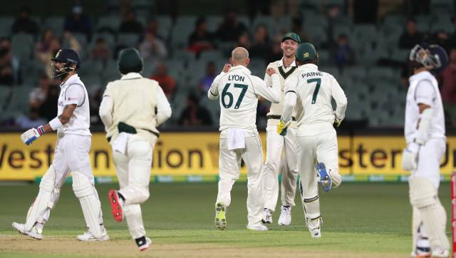 Australia's Nathan Lyon, center, celebrates with teammates after running-out India's Virat Kohli, left, during their cricket test match at the Adelaide Oval in Adelaide, Australia, Thursday, Dec. 17, 2020. (AP Photo/James Elsby)