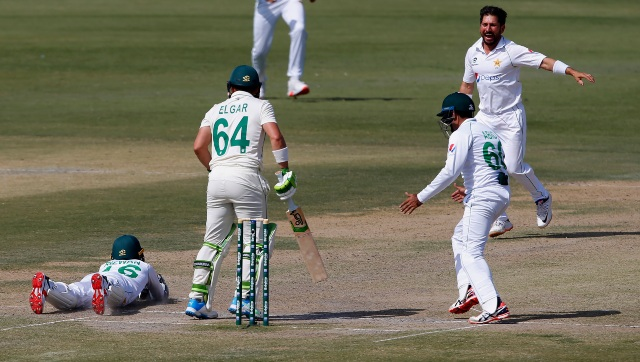 Pakistan's Yasir Shah, and Abid Ali celebrate while teammate Mohammad Rizwan, left, takes the catch of South Africa's Dean Elgar during the third day of the first Test match between Pakistan and South Africa. AP
