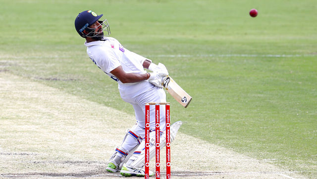 India's Cheteshwar Pujara avoids a bouncer while batting during play on the final day of the fourth cricket test between India and Australia at the Gabba, Brisbane, Australia, Tuesday, Jan. 19, 2021. (AP Photo/Tertius Pickard)