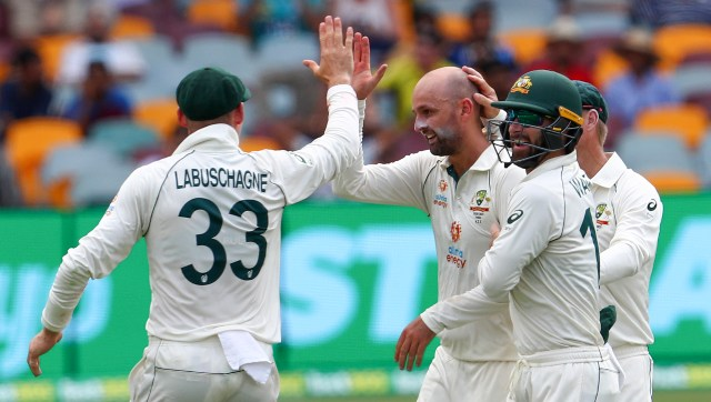 Australia's Nathan Lyon, left, is congratulated by teammate's Matthew Wade and Marnus Labuschagne, left, after taking the wicket of India's Rohit Sharma. AP